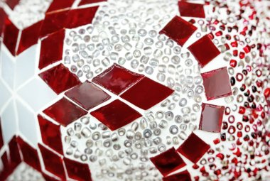 Textured fragment of stained glass with a geometric red-and-white pattern.