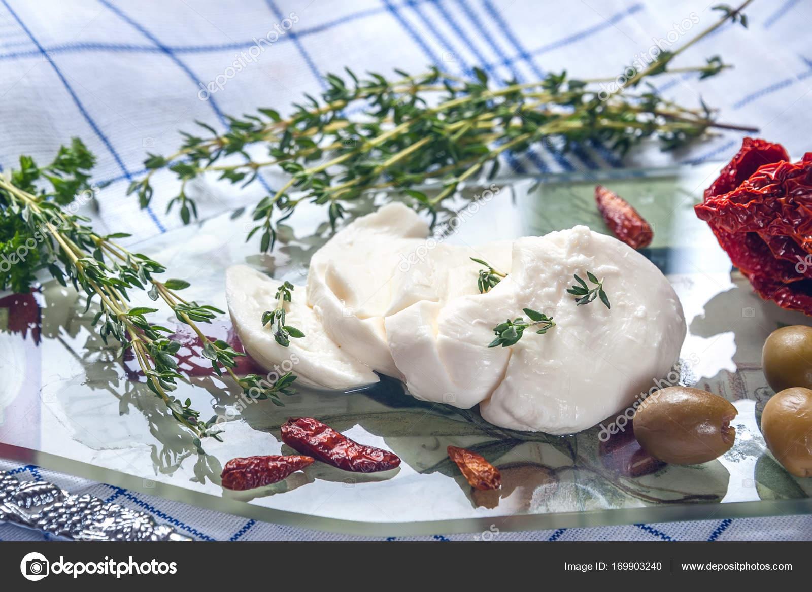 Tagliare un pezzo della mozzarella con timo erba, peperoncini e ...
