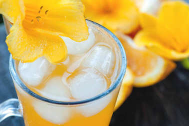 Cold orange juice with ice, decorated with a yellow Lily flower close-up.