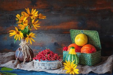Beautiful autumn still life from different pumpkins in a wicker basket, yellow daisies in a clay ceramic brown ethnic vase on wooden table in rustic style.