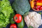 Míchaná zelenina z květáku a brokolice, česnek, cibule, rajčata a zelený hrášek na dřevěné pozadí v rustikálním stylu.