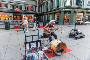 Oslo, Norway-August 1, 2013: a street musician performs on the main street of Karl Johans gate. An elderly man with long white hair, earns money on the street playing the guitar and singing. Editorial