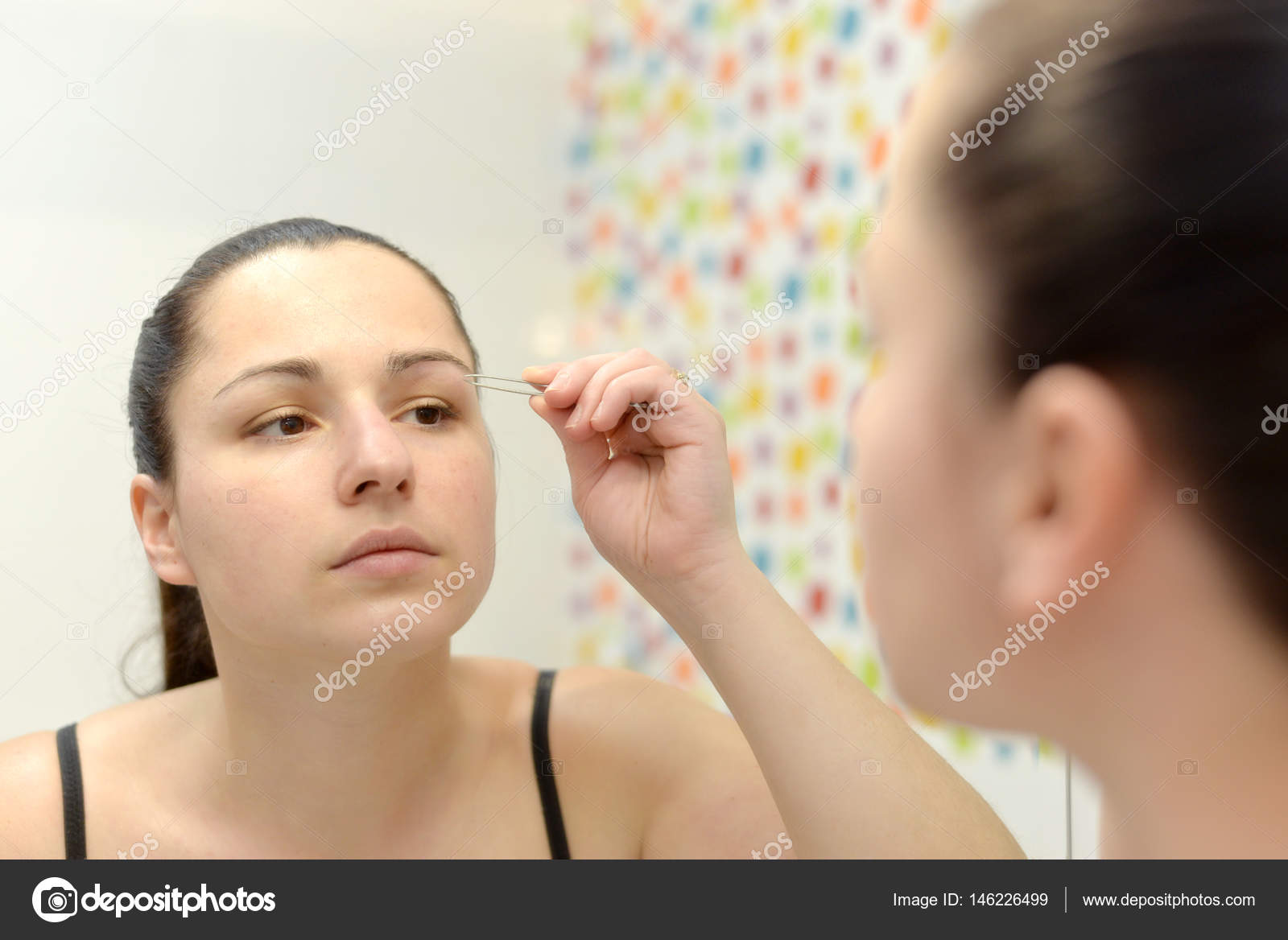 Woman Shapes Her Eyebrows And Looking In The Mirror In The Bathr