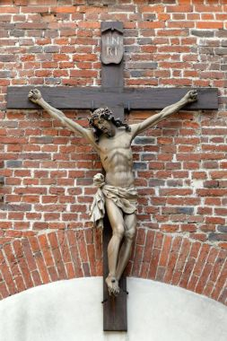 Crucifix on brick wall. Jesus Christ on cross. Religious, belief and hope. Holy and sacred places.