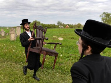 Belz, Ukraine - May 11, 2015: Ultra-orthodox Jews prayed on tombs of Tazdikim in Belz town, Lviv region. stock vector