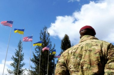 American Soldiers and flags of the Ukraine and USA at background