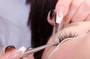 Beautiful young woman or teenager extends eyelashes in salon