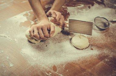 Female hands pressing dough