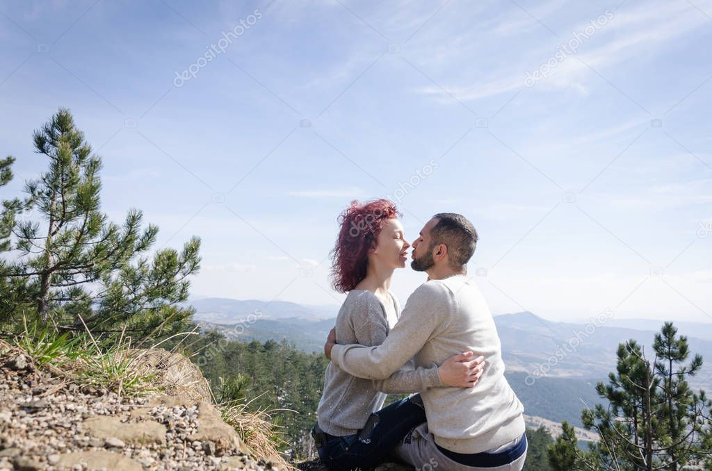 boy and girl sit cuddled on the mountain