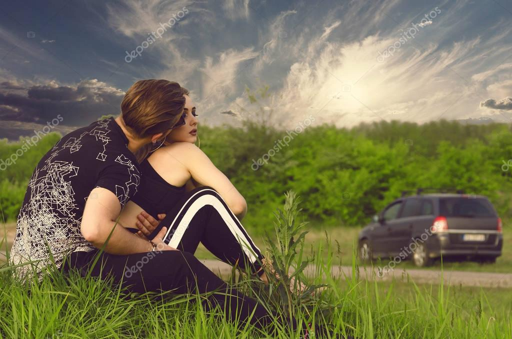 boy and girl sitting next to the highway