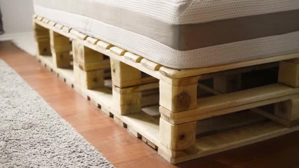 Detail dřevěné postele s šedý koberec v pokoji