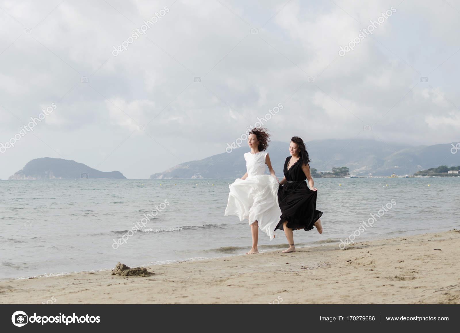 a40207ce554 Δύο γυναίκες σε μαύρο και άσπρο κομψό φορέματα τρέχει με τον άνεμο στην  αμμώδη παραλία κοντά στη θάλασσα. Φέρουν τρίχωμα — Εικόνα από ...
