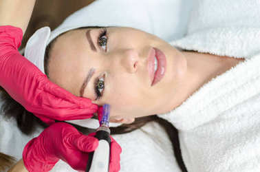 Beautician performs a micro needle mesotherapy treatment on face.