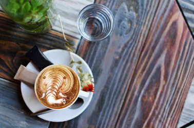 Latte art, coffee art made by barista on beautiful retro wooden background, view from above or top. Copy space for text