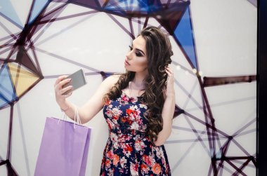 happy woman with smartphone taking selfie at clothing store in mirror