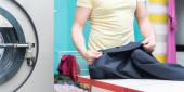 Mann nimmt saubere Kleidung an der Reinigung