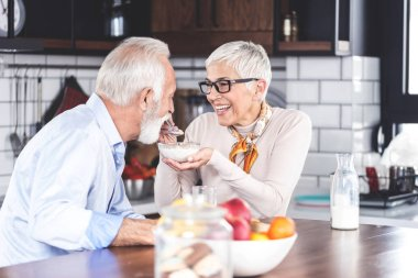 Senior couple enjoying their time at home in kitchen with breakfast in morning