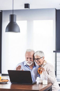 Two senior people making video call on digital tablet in modern kitchen