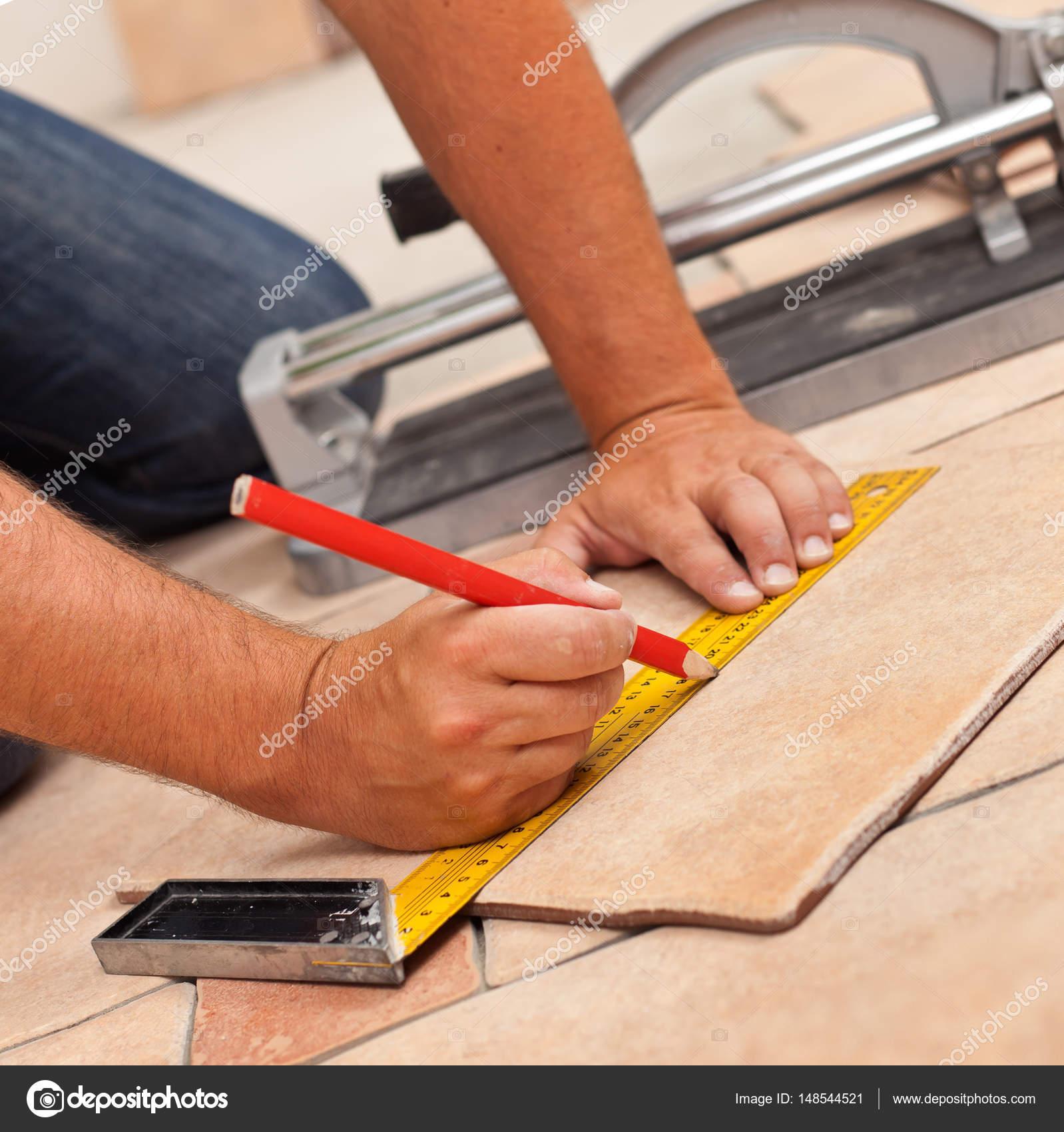 Laying ceramic floor tiles man hands marking tile to be cut c laying ceramic floor tiles man hands marking tile to be cut c stock dailygadgetfo Choice Image