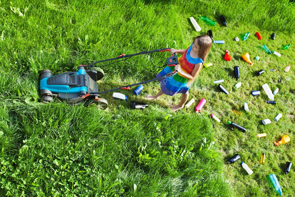 Young girl pushing a lawnmower and leaving plastic litter behind