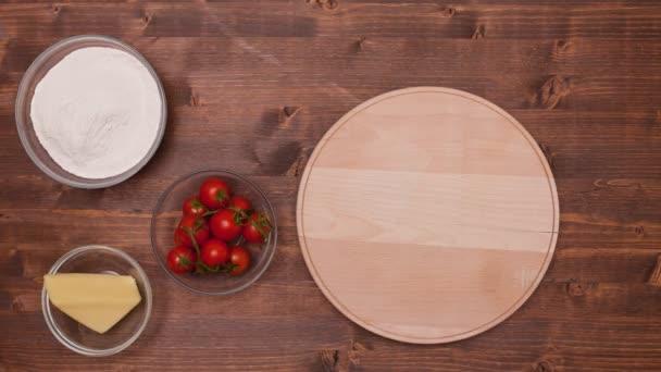 Pohled shora pizzy s ingrediencí společně v miskách na dřevěný stůl, stop-motion animace