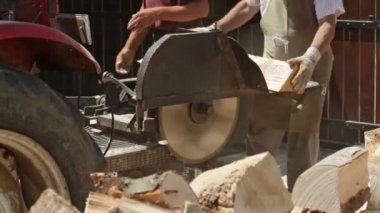 Close up of movement along of male workers cutting firewood logs with circular saw