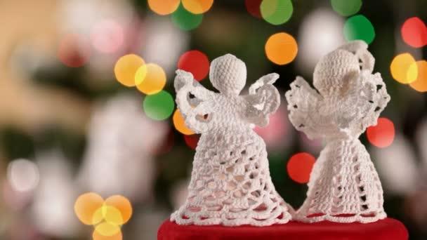 Zblízka dva vánoční andělé na rozostřeného pozadí vánoční světla