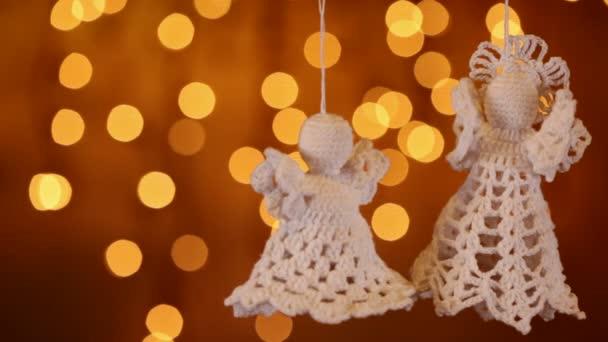 Dvě háčkované vánoční ozdoby andělé zavěšení na pozadí rozmazané světla