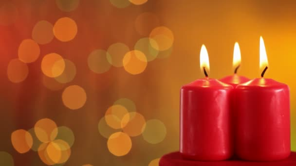 Close up of three burning christmas candles on colorful blurred background