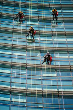 MILAN, ITALY - SEPTEMBER 19,2017: Climber workers for glass cleaning at Porta Garibaldi district, Piazza Gae Aulenti.