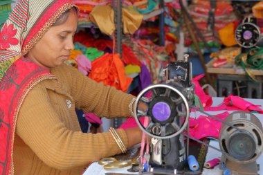 CHITTORGARH, RAJASTHAN, INDIA - DECEMBER 13, 2017: Close-up on a tailor woman working on her sewing machine inside her shop in the Old Town