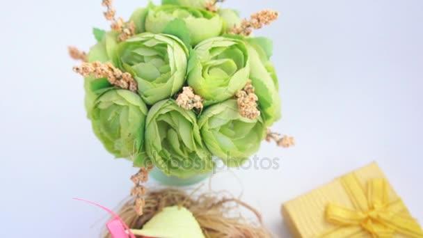 Velikonoční vejce v slaměném hnízdě a jarní květiny