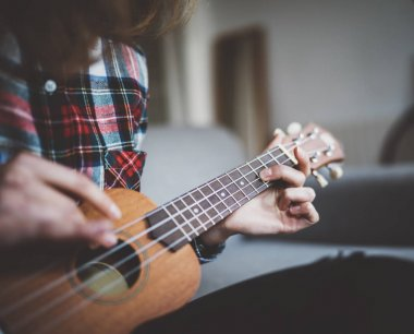 young girl learning to play ukulele