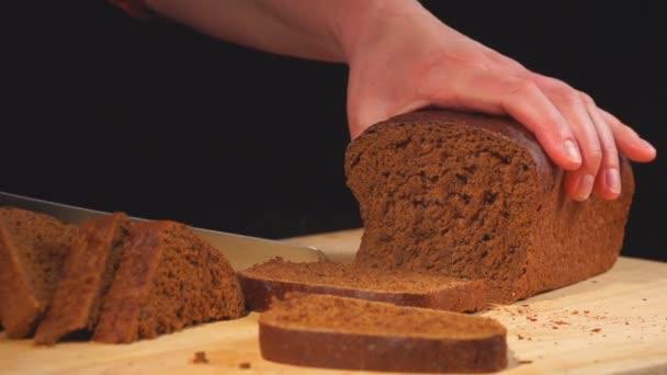 Brotscheiben in Zeitlupe auf Holzbrett schneiden. Männliche Hände schneiden selbstgebackenes Brot auf Holztisch.