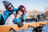 Paar Snowboarder umarmen sich