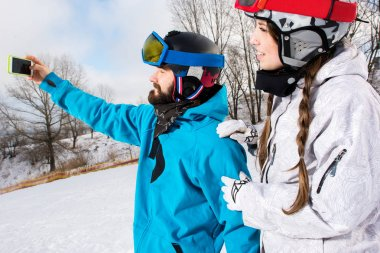 Young smiling couple of snowboarders taking selfie with smartphone stock vector