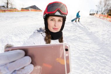 Beautiful young female snowboarder taking selfie with smartphone stock vector