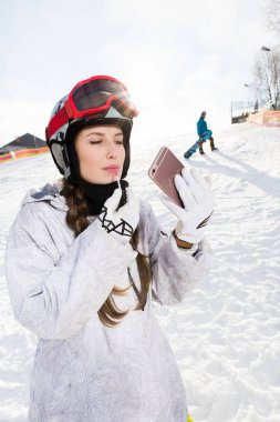 Attractive young female snowboarder applying lip gloss while looking at smartphone stock vector