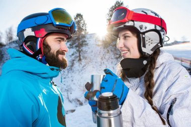 Side view of snowboarders drinking hot tea from thermos and looking at each other stock vector