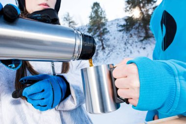 Close-up partial view of snowboarders pouring hot tea from thermos in cup stock vector