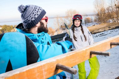 Young male and female snowboarders at ski resort  looking at each other stock vector