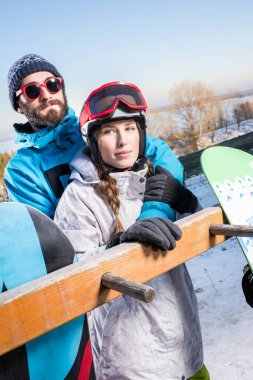 Young male and female snowboarders embracing and looking at camera stock vector