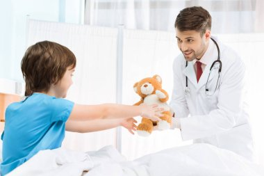 Side view of doctor giving teddy bear to child patient stock vector