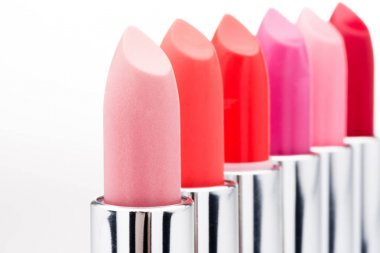Close-up view of fashionable lipsticks in red and pink colors in a row isolated on white stock vector