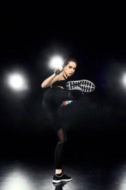 attractive sportswoman kicking