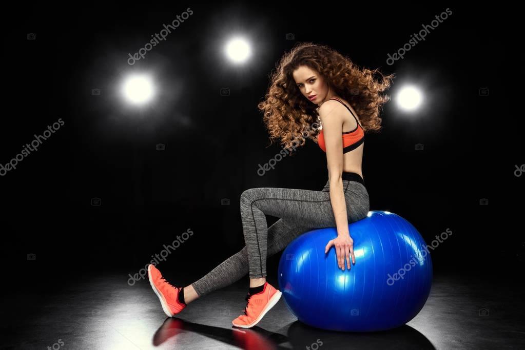 sportswoman sitting on fitness ball