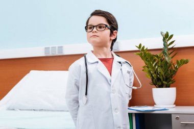 Confident boy doctor in medical uniform looking away in hospital room stock vector