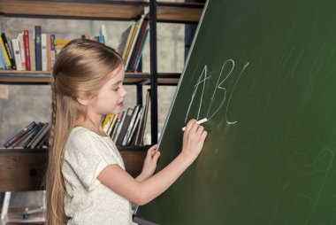 Girl writing on chalkboard
