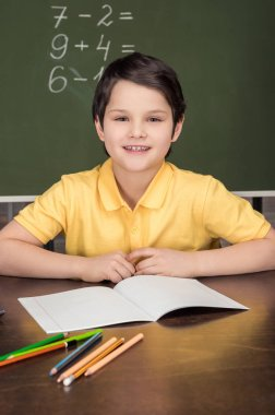 boy sitting at table in classroom