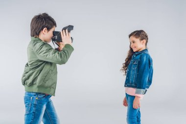 Boy taking pictures of girl
